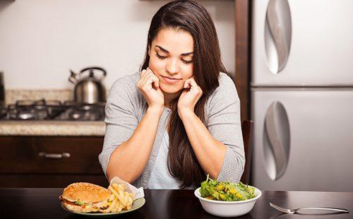 Темноволосая девушка смотрит на гамбургер