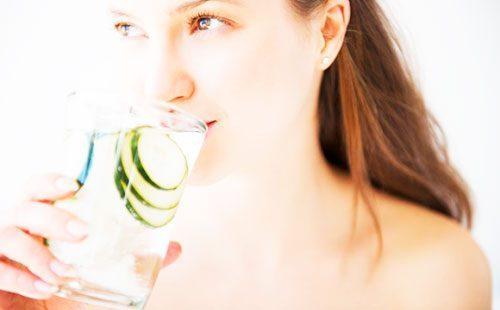 Девушка пьет воду с огурцами