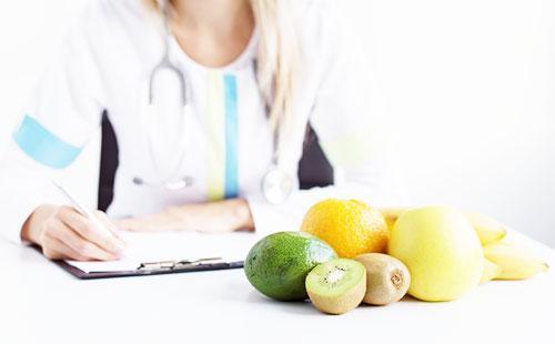 Врач и фрукты на столе