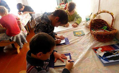 Дети сидят за столом и рисуют