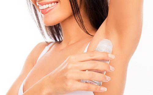Красивая улыбка девушки с дезодорантом