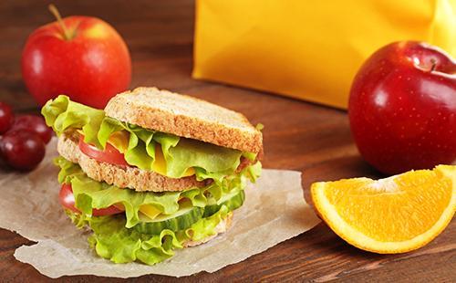 Бутерброд с зелёным салатом, долька апельсина и красные яблоки на завтрак