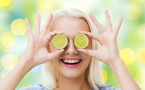 Девушка держит два кружочка лимонов