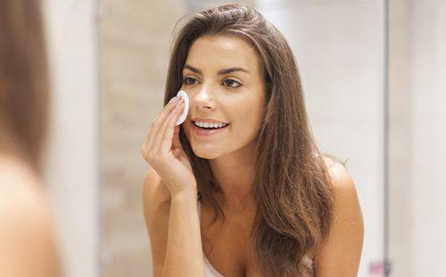 Темноволосая девушка стирает макияж ватным диском