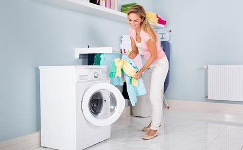 Молодая женщина возле стиральной машины