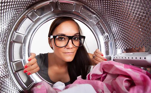 Девушка заглядывает внутрь стиральной машины