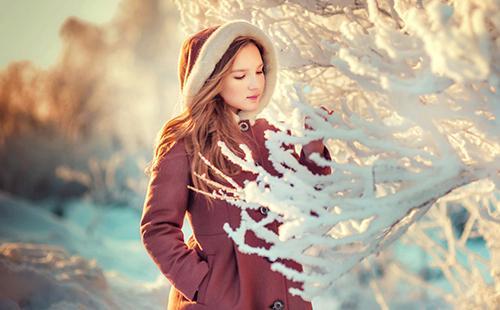 Юная девушка любуется заиндевевшими ветвями