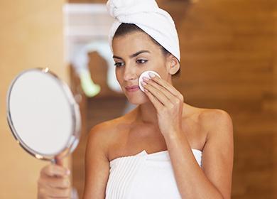 Женщина смотрит в зеркало и протирает лицо