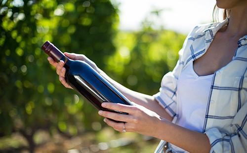 Женщина на природе держит бутылку вина