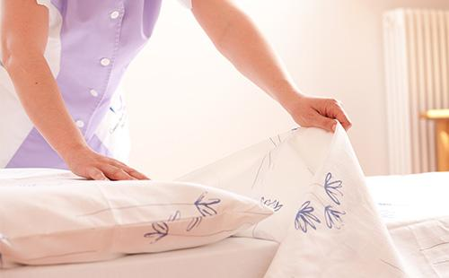 Женщина застилает кровать