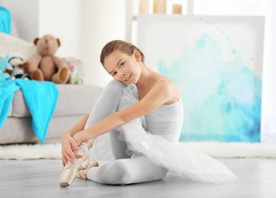 Милая маленькая балерина сидит на полу