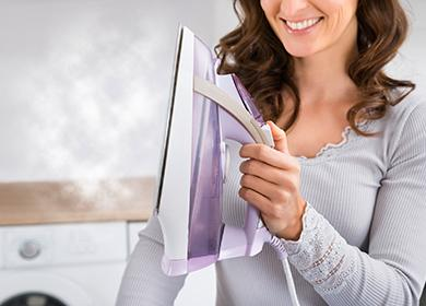 Смеющаяся женщина держит на весу паровой утюг