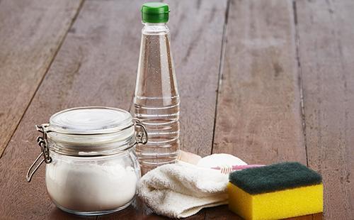 Уксус, сода и губка на деревянных досках