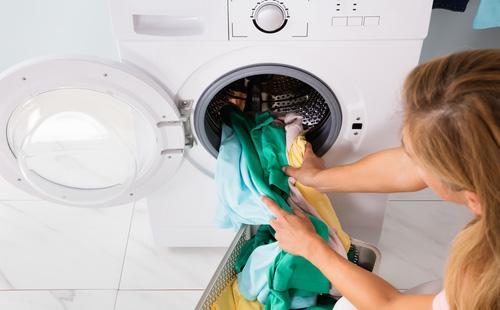 Женщина закладывает вещи в стиральную машину