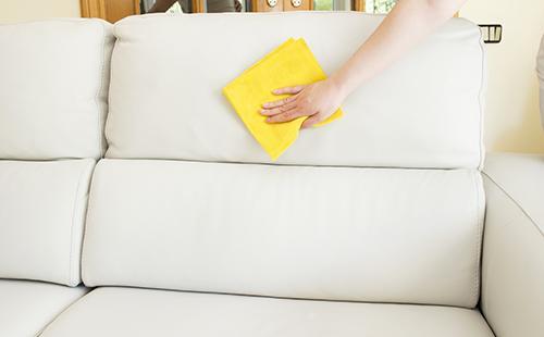 Рука протирает светло-бежевый диван жёлтой салфеткой