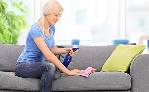 Домохозяйка тряпочкой протирает мебель