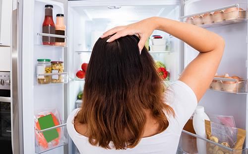 Растерянная женщина заглядывает в холодильник