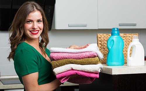 Довольная домохозяйка со стопкой чистого белья