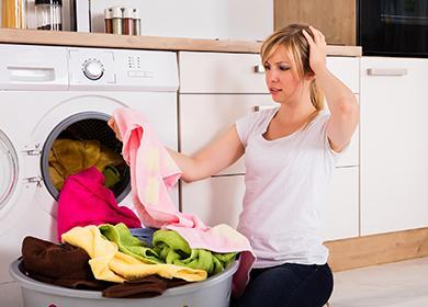 Женщина у стиральной машины с ужасом смотрит на бельё