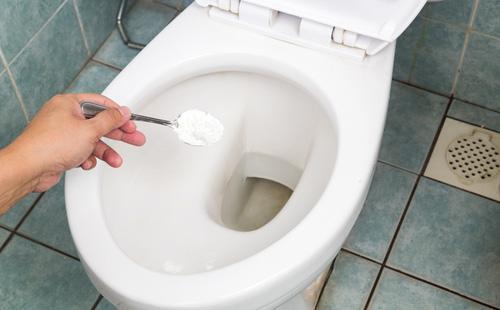 Сода в ложке для мытья унитаза