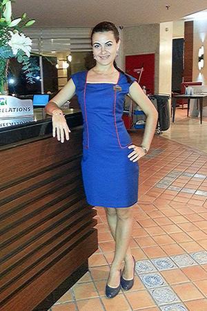 Надежда в синем платье стоит у стойки