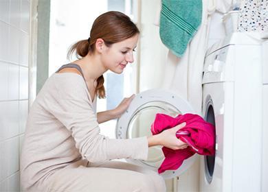 Женщина кладет красную кофту в стиральную машину