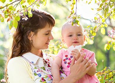 Мама с малышкой гуляют среди цветущих деревьев