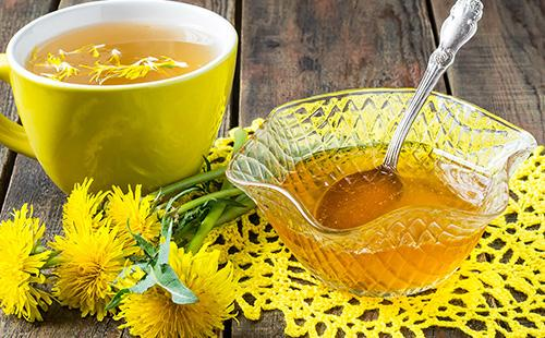 Сладкое лакомство в розетке и чашка цветочного чаю