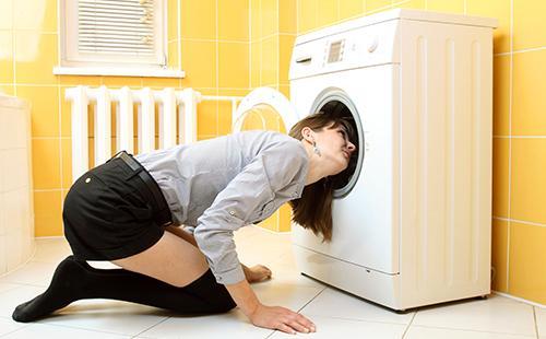 Женщина сидит на полу и заглядывает в машинку