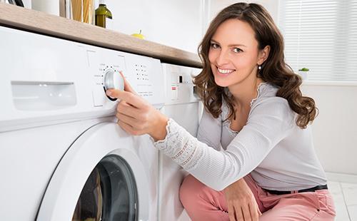 Женщина с улыбкой включает стиральную машину