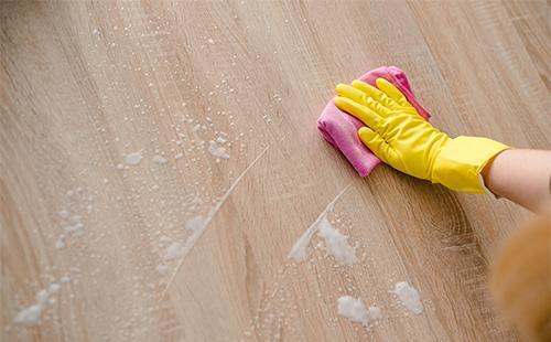 Рука в перчатке моет тряпкой ламинат