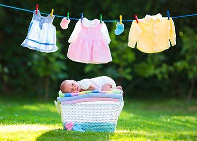 Младенец лежит на стопке чистого белья
