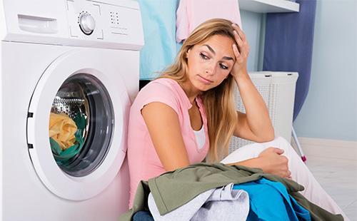 Женщина сидит возле стиральной машины