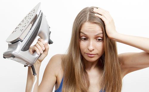 Женщина с утюгом держится за голову
