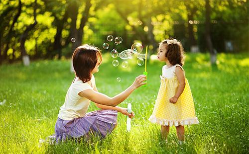 Мама с дочкой играют мыльными пузырями