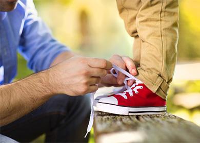 Отец завязывает сыну шнурки