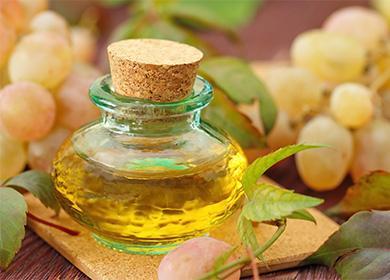 Масло в баночке на фоне зеленого винограда
