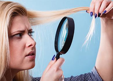 Женщина смотрит на волосы через лупу
