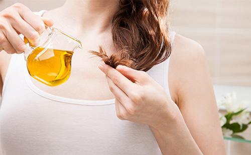Женщина льет масло на волосы