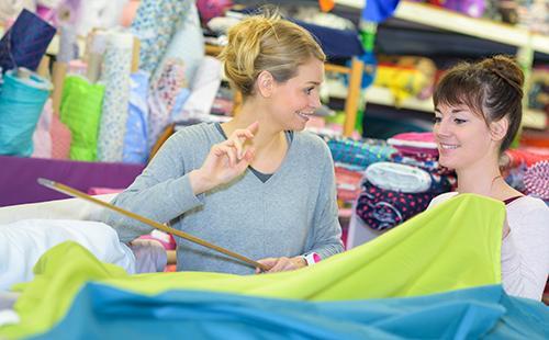 Женщина в магазине выбирает ткань