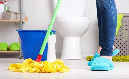Женщина с жёлтой шваброй в ванной комнате
