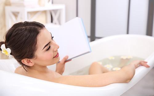 Девушка читает, принимая ванну