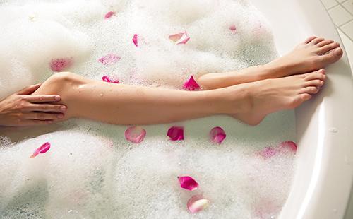 Девичьи ноги в пенистой ванне с розовыми лепестками