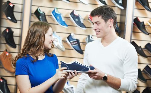 Женщина выбирает обувь в магазине