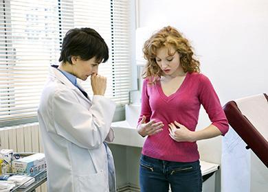 Девушка на приёме у врача показывает на свой живот
