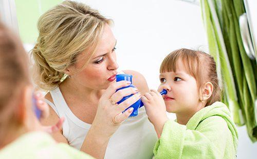 Мама помогает малышке промывать носик