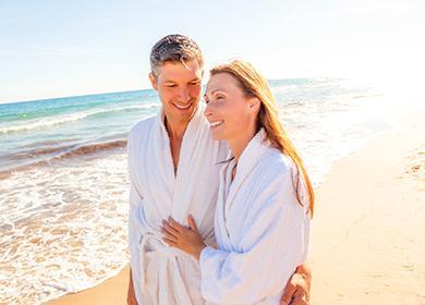 Счастливая пара в халатах на берегу моря