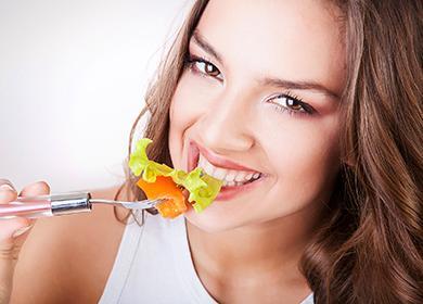 Красивая девушка ест салат
