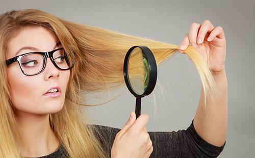 Блондинка рассматривает свои волосы в лупу