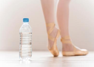 Бутылка воды и танцующие ноги балерины на заднем плане